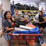 Three women hold shopping carts filled with supplies from the MFTA warehouse.