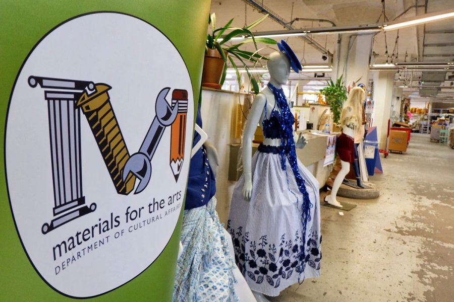 "Close up of the green MFTA banner in the MFTA warehouse. The banner displays the MFTA logo with the words ""Materials for the Arts Department of Cultural Affairs"" beneath. Dressed up mannequins are to the right of the sign."