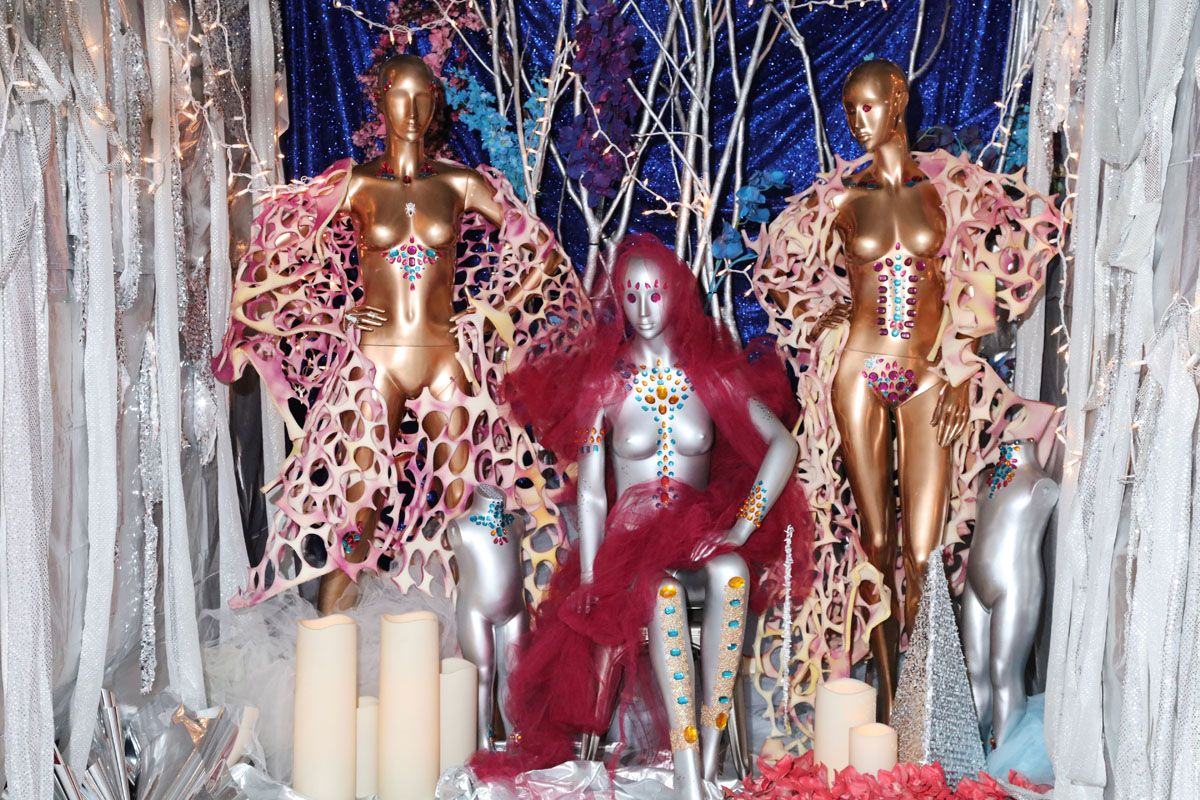 Two bronze and one silver mannequin stand bedazzled with jewels and fabric. Behind them is blue draped fabric and cut strips of silver flow on either side of them. Fairy lights and tree branches are in the background. Large candles rest at the mannequins' feet.