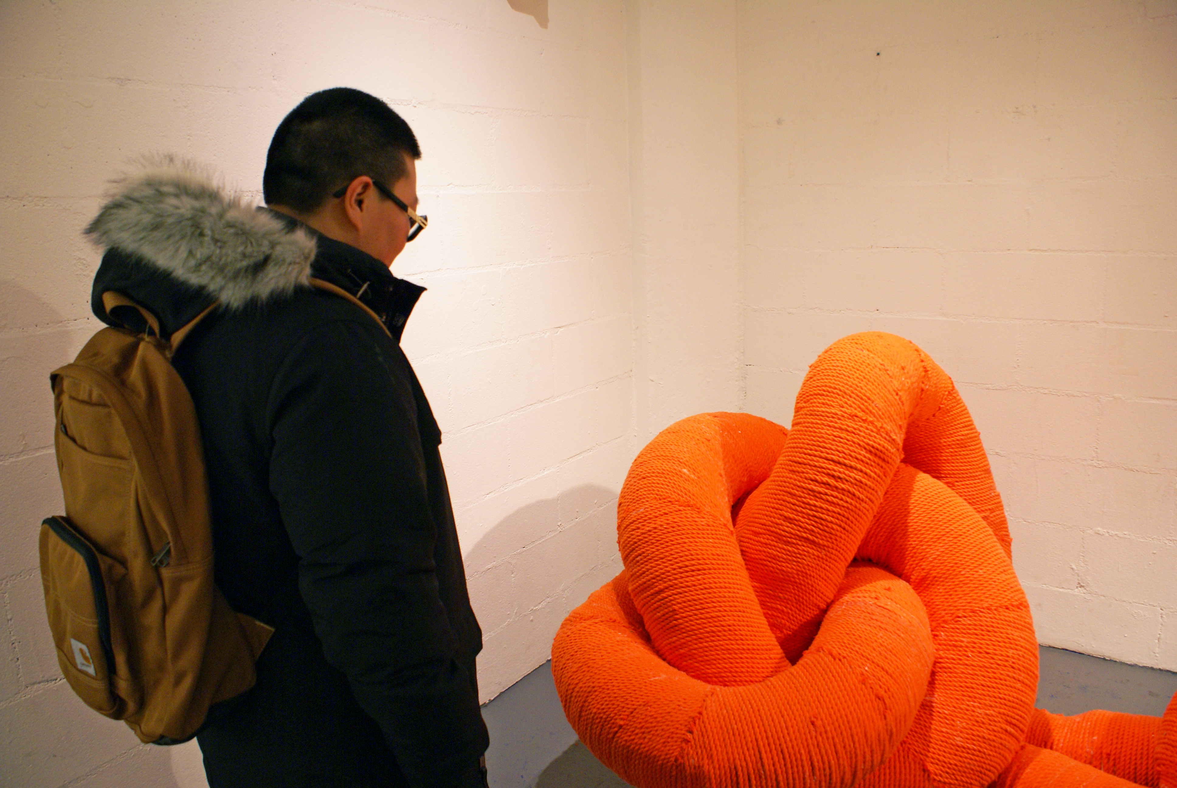 Woman looks at Whitney Oldenburg's sculpture titled Shoe Lace in the MFTA Gallery. The sculpture is made of intertwined ventilation tubing covered in bright orange yarn-like cord.